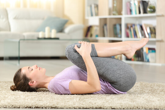 Profile of a woman doing yoga exercise at home