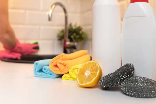 Cleaning products, citron and sponges on kitchen countertop with in focus and in background blurred womens hands cleaning kitchen.