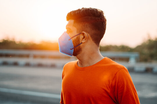 Portrait of an Indian bearded man looking sideways while wearing n95 face mask in front of the sun with lens flare of sun besides him during the sunrise