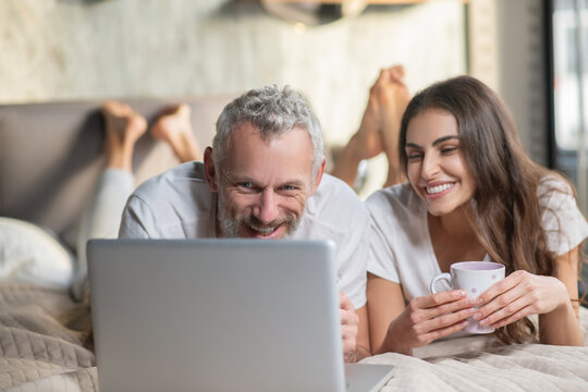 Couple staying in the bed with coffee and computer