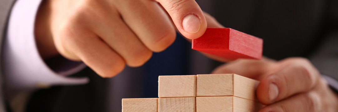 Close up of businessman in suit making a wooden cubes pyramid. Business and strategy concept