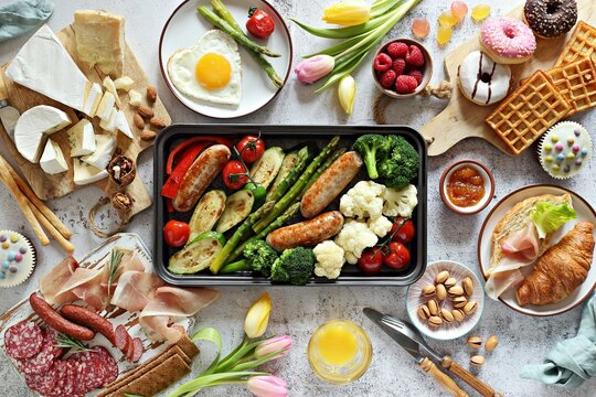 Breakfast food table. Festive brunch set, meal variety with grill platter, fried egg, croissant sandwich, cheese platter and desserts. Overhead view