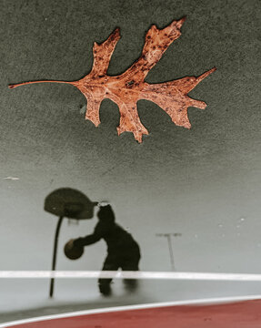 Reflection of Someone Playing Basketball in the Rain
