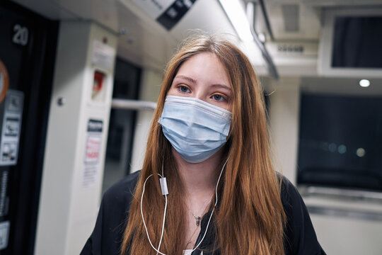 A beautiful white Latina woman using the city subway with a fixed look on her face wearing a covid 19 mask and listening to music
