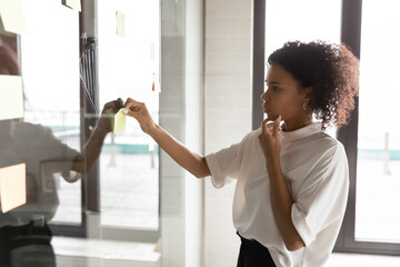 Close up thoughtful African American businesswoman adding colorful sticky paper on glass board,...