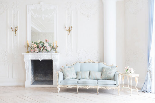 luxurious light interior in the Baroque style. A spacious room with a road chic beautiful furniture, a fireplace and flowers. plant stucco on the walls and light wood parquet