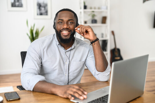Smiling young African American call center manager wearing a headset and looking at the camera, checking the microphone, e-commerce manager receiving calls from customers, typing on the laptop