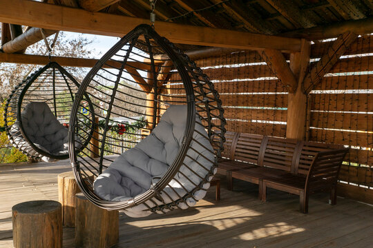 two big comfortable rotang round hanging chairs with grey pillow on outdoor wooden backyard, relaxing lesure concept