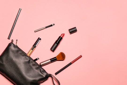 Fashionable flat lay shot with makeup products: cosmetic case, lipstick, eyeliner, brush, highlighter, and lip pencil on a pastel pink background.