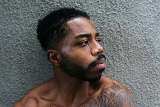 Thoughtful shirtless athlete looking away against gray textured wall