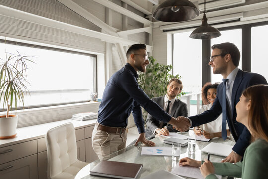 Diverse business partners shaking hand in modern boardroom after negotiation, signing contract, making successful deal, Arabian executive greeting new employee at meeting, group negotiations