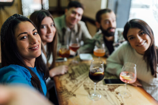 Smiling friends with drinks taking selfie at restaurant