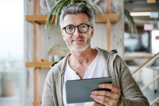 Man wearing eyeglasses using digital tablet