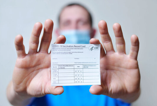 male is holding a vaccination record card and corona virus vaccine vials. Passport of immunity to the coronavirus in the hands of a male. Health passport as proof of recovery from COVID-19.