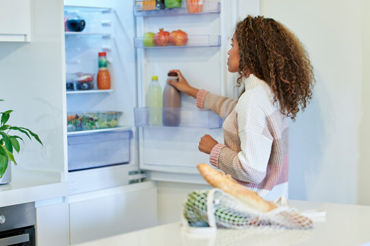 Afro young woman placing groceries into refrigerator at home