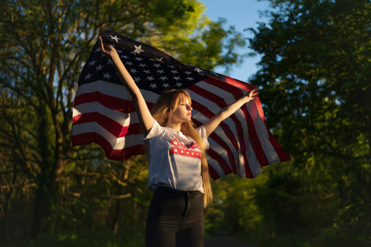 Blond woman holding American flag while standing with eyes closed at forest
