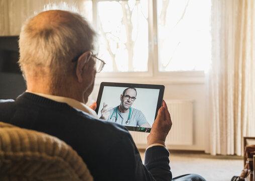 Male general practitioner advising senior man on video call through digital tablet in living room