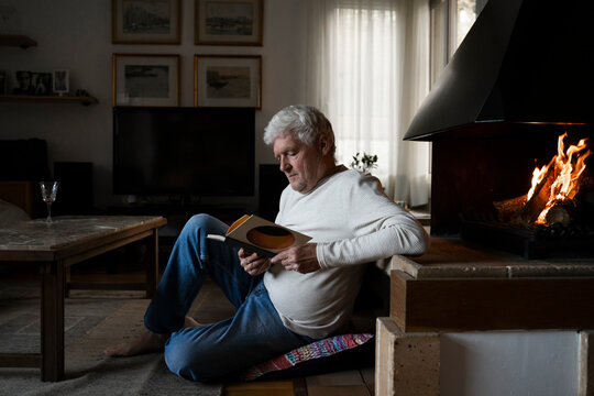 Senior man reading book while sitting on floor at home
