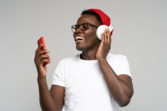 Happy African American man with headphones wear red hat and glasses, enjoying listening to the artist's new album, using phone, dancing, makes movements to music, isolated on studio grey background.