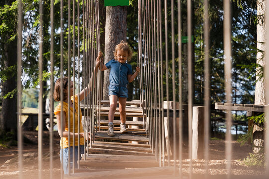 Mother assisting little daughter walking across small suspension bridge on forest obstacle course