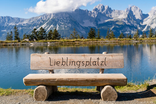 Empty wooden bench on shore of alpine lake in Kaiser Mountains