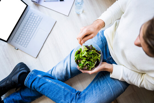 Young man with laptop holding plastic container of salad in new loft apartment
