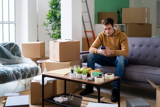 Young man using smart phone while moving in new loft apartment