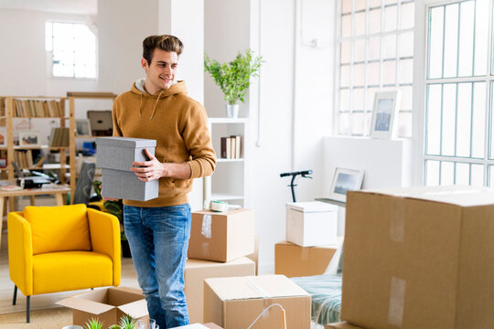 Smiling young man holding boxes while standing in new loft apartment