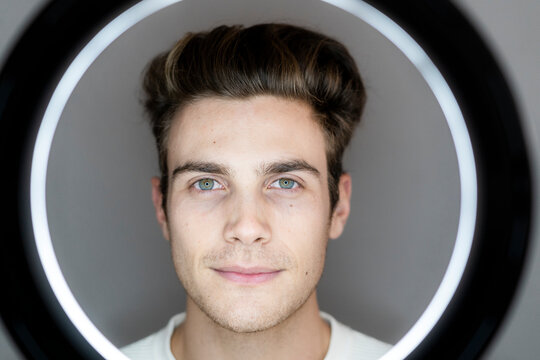 Young male influencer seen through circle light against gray background