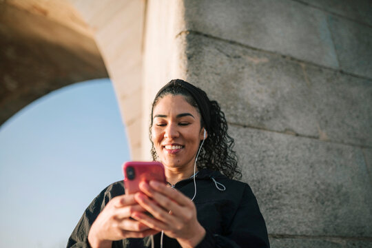 Smiling sportswoman using mobile phone while listening music against wall