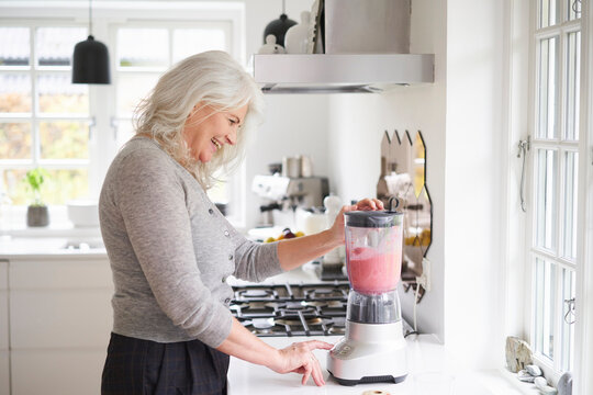Happy retired woman preparing strawberry smoothie in processor at kitchen counter