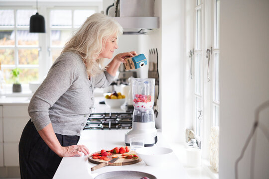 Senior woman pouring milk in processor while preparing strawberry smoothie at kitchen