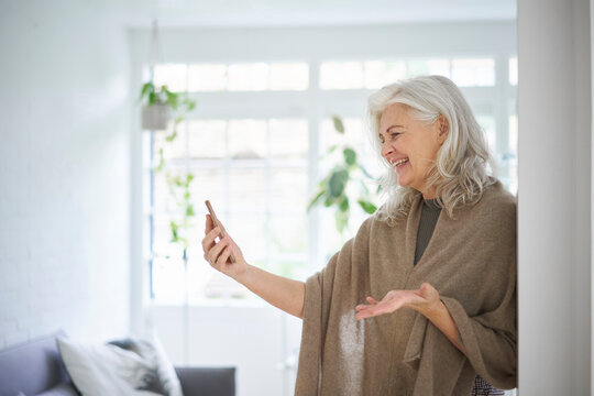Happy retired woman on video call through smart phone at home