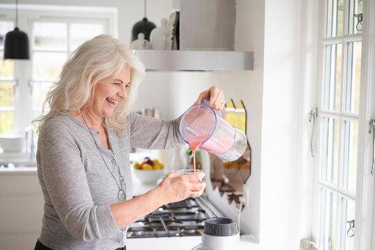 Cheerful senior woman pouring strawberry smoothie in glass at kitchen