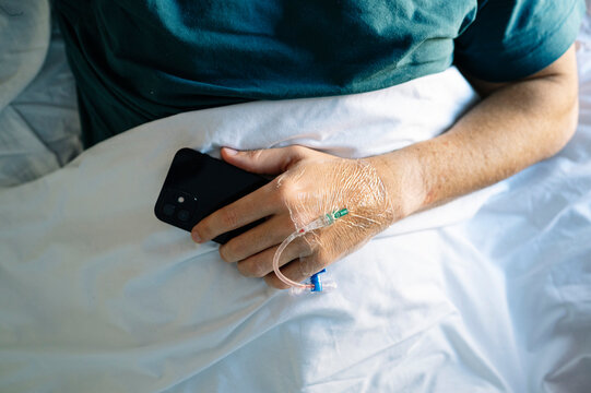 Patient holding mobile phone with IV drip hand lying on bed in hospital