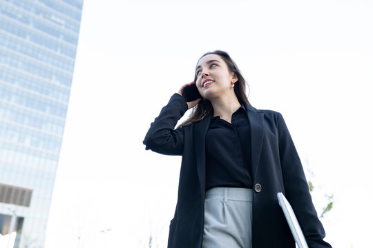 Young businesswoman with laptop looking away while talking on mobile phone standing against sky