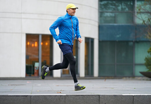 Cheerful mature man in sports clothing jogging on footpath