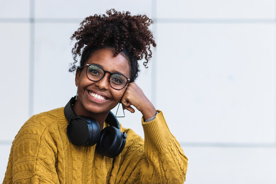 Happy afro young woman in sweater wearing headphones against white wall