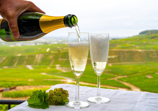 Tasting of french sparkling white wine with bubbles champagne on outdoor terrace with view on grand cru Champagne vineyards in Cramant, near Epernay, France