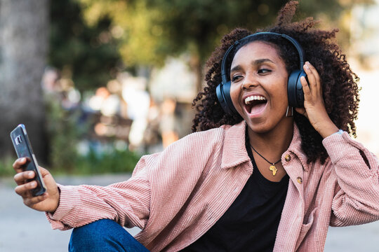 Cheerful young woman with mouth open taking selfie with headphones in city