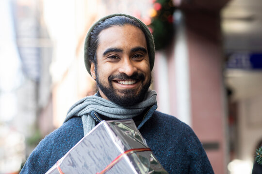 Close-up portrait of bearded young man with Christmas present
