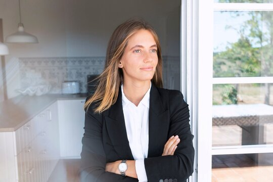Thoughtful young businesswoman with arms crossed leaning on door while looking away