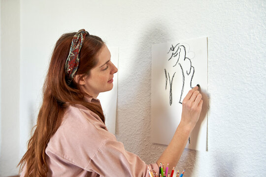 Smiling female artist drawing with charcoal on paper pasted on wall at home