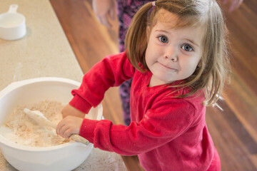 Little girl helping cook ANZAC biscuits