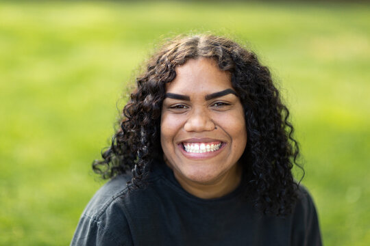smiling young woman wearing black against green grass background