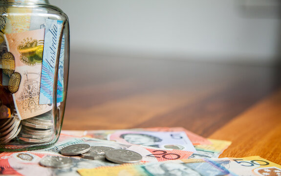 Australian money in notes and coins on wooden background with jar