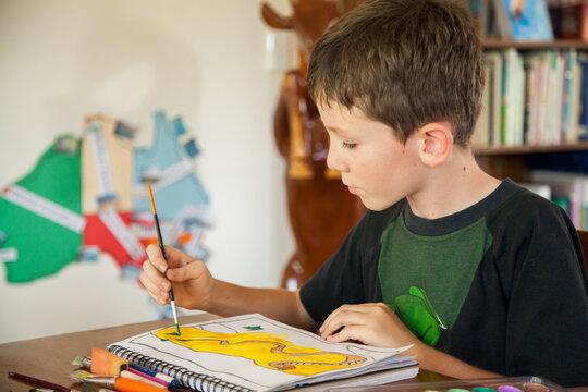 Australian boy painting in art class