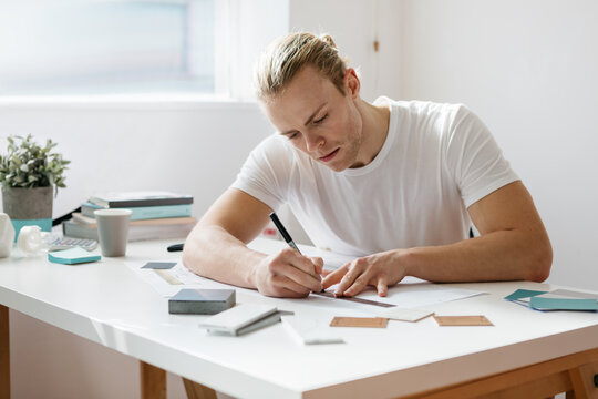 Young architect guy working on drawings in an office