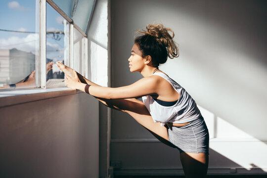 Beautiful 20s girl stretching her leg in a dance studio