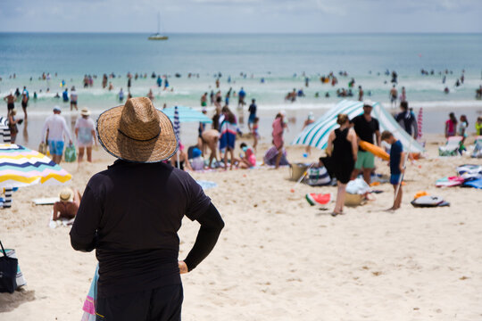 Man wearing a straw hat and rashie at noosa main beach